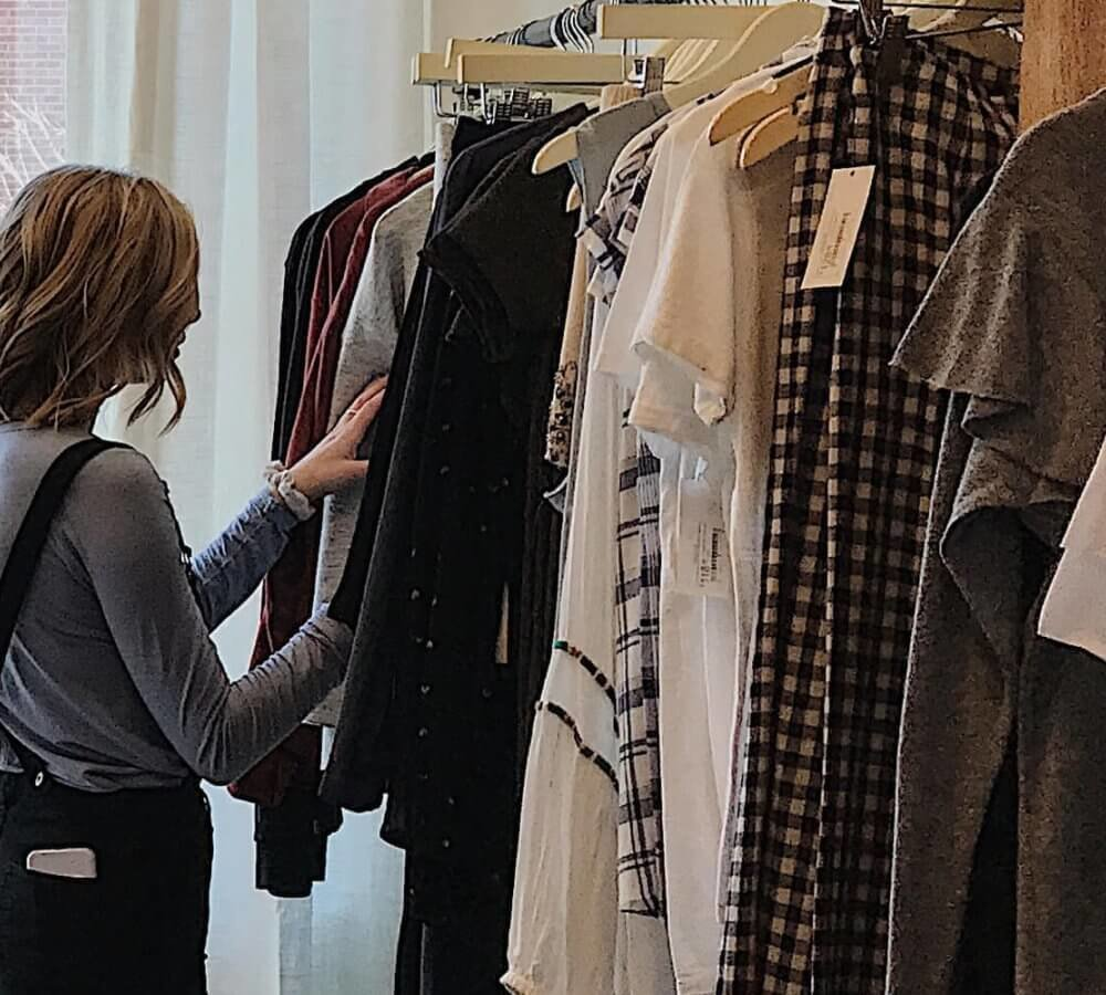 Woman looking through rack of clothes